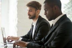 Caucasian affärsman som ser bärbara datorn av afrikansk amerikancoll royaltyfri fotografi
