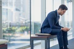 Caucasian affärsman som ser mobiltelefonen, medan sitta på bänk i modernt kontor fotografering för bildbyråer