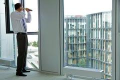 caucasian affärsman som spionerar genom att använda teleskopet till och med kontorsfönster royaltyfria bilder