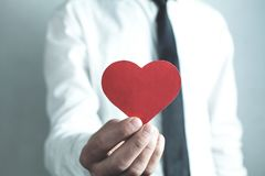 Caucasian affärsman som visar röd hjärta mig min jobbförälskelse royaltyfri foto
