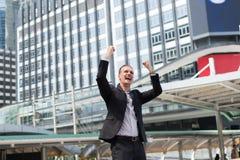 Caucasian affärsmanställning och lyfta upp två händer till gladlynt och som firar hans lyckat i beskickning fotografering för bildbyråer