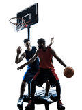 Caucasian and african basketball players man dribbling silhouett. Two men basketball players competition dribbling in silhouette isolated white background Stock Photo
