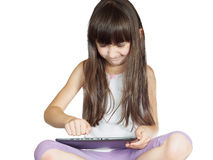Caucasian angry child kid girl sister sitting on the bed with tablet pc isolated Royalty Free Stock Photography