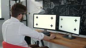 Caucasian arbetarmaskinskrivning på tangentbordet och se den gröna skärm20-tal 4k lager videofilmer