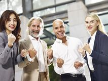 Multiethnic corporate executives showing determination and team. Caucasian asian latino corporate business people making a fist showing determination and team Royalty Free Stock Photography