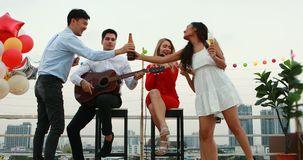 Caucasian and Asian people in roof top party. In roof top party, Caucasian man playing guitar, Caucasian woman singing songs, Asian woman pouring alcohol to her