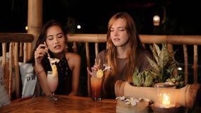 Caucasian and asian women chatting in a bar with drinks, smiling. Slider stock video footage