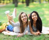 Caucasian and Asian young woman doing selfie and showing tongues. Caucasian and Asian young women doing selfie and showing tongues. Funny girl friends having fun Stock Image