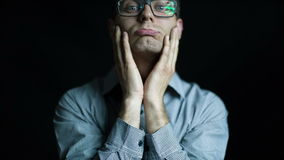 Caucasian attractive man in glasses pucker bored portrait on black background Royalty Free Stock Images