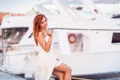 Caucasian attractive redheaded girl in white summer dress. Sits by the berth with yachts and looks at the camera Stock Photos