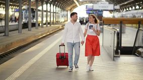 Caucasian attractive wife and husband walking on a railway station with suitcases on wheels and talking while having stock footage