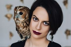 Caucasian attractive woman with make up in black dress with owl on her shoulder, portrait of future mother, fashion Royalty Free Stock Image