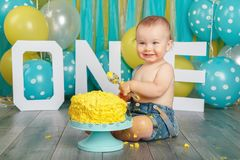 Caucasian baby boy celebrating his first birthday. Cake smash. Portrait of cute adorable Caucasian baby boy in jeans pants celebrating his first birthday. Cake stock photos