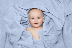 Caucasian baby boy covered with green towel joyfully smiles at c Stock Images