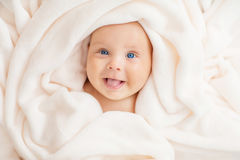 Caucasian baby boy covered with towel. Caucasian baby boy covered with white towel joyfully smiles at camera stock photography
