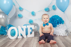 Caucasian baby boy in dark pants and blue bow tie celebrating his first birthday with letters  one and balloons Royalty Free Stock Image