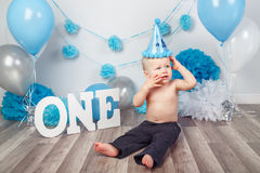Caucasian baby boy in dark pants and blue bow tie celebrating his first birthday with letters  one and balloons Stock Photography