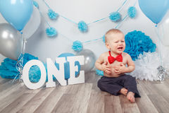 Caucasian baby boy in dark pants and blue bow tie celebrating his first birthday with letters  one and balloons Royalty Free Stock Images