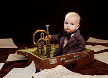 Caucasian baby boy plays with trumpet Stock Images