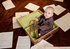 Caucasian baby boy plays with trumpet Stock Photos