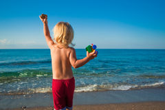Caucasian baby boy throw stones to the sea Stock Photography