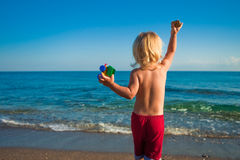 Caucasian baby boy throw stones to the sea Stock Photo