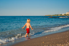 Caucasian baby boy walk on the beach Stock Photos