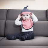 Caucasian baby boy weared bib  sitting on sofa at home Stock Photo