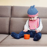 Caucasian baby boy weared bib  sitting on sofa at home Royalty Free Stock Photo