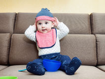 Caucasian baby boy weared bib  sitting on sofa at home Royalty Free Stock Images