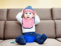 Caucasian baby boy weared bib sitting on sofa at home stock photos
