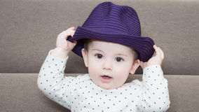 Caucasian baby boy weared a hat sitting on sofa at home Stock Photo