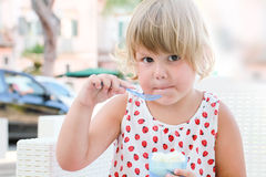 Caucasian baby girl eats frozen yogurt, closeup Royalty Free Stock Photos