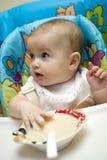 Caucasian baby girl feeding herself Stock Image