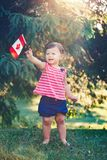 Caucasian baby girl holding Canadian flag with red maple leaf. Portrait of little white Caucasian baby girl holding Canadian flag with red maple leaf. Toddler stock photo