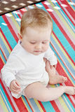 Caucasian baby girl sitting on a colorful blanket Royalty Free Stock Photography
