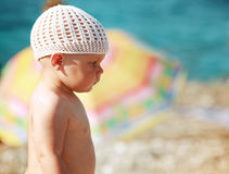 Caucasian baby girl in white hat on the beach Royalty Free Stock Image
