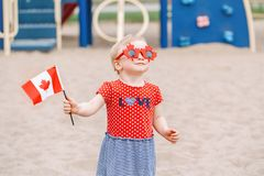 Caucasian baby toddler girl holding Canadian flag. Portrait of adorable cute little blonde Caucasian baby toddler girl holding Canadian flag. Female child royalty free stock photos