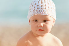 Caucasian baby in white hat on the beach Royalty Free Stock Photos
