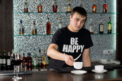Caucasian barman serving coffee at the bar Royalty Free Stock Photos