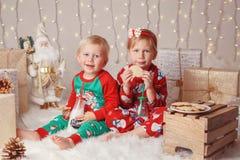 Caucasian barnsyskongrupp i tröjor som sitter tillsammans att krama fira jul eller nytt år royaltyfri fotografi