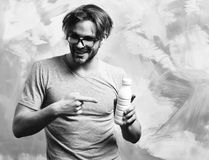 Caucasian bearded macho man holding bottle of milk. Bearded man, short beard. Caucasian amused macho with moustache in glasses wearing gray shirt holding plastic stock photos