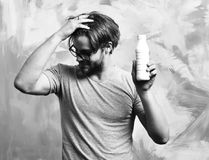 Caucasian bearded macho man holding bottle of milk. Bearded man, short beard. Caucasian amused macho with moustache in glasses wearing gray shirt holding plastic royalty free stock photo