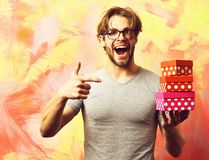 Caucasian bearded macho man holding gift boxes. Bearded man, short beard. Caucasian amused macho with moustache in glasses wearing gray shirt holding set of gift stock image