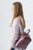 Caucasian beautiful girl with long brown hair with backpack of marsala color. Stock Photography