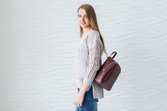 Caucasian beautiful girl with long brown hair in grey pullover with backpack of marsala color. Cheerful studio portret Royalty Free Stock Images
