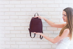 Caucasian beautiful girl with long brown hair holding backpack of marsala color. Royalty Free Stock Photos