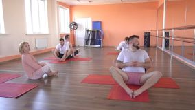 A caucasian beautiful girl trainer conducts a group yoga class among male friends in a modern fitness center, developing. Breathing practices, slow motion stock video footage