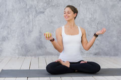 Caucasian beautiful healthy athletic sportive girl eat green apple after the training and looking at camera.  Stock Images