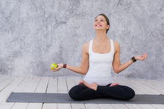 Caucasian beautiful healthy athletic sportive girl eat green apple after the training and looking at camera.  Royalty Free Stock Photos